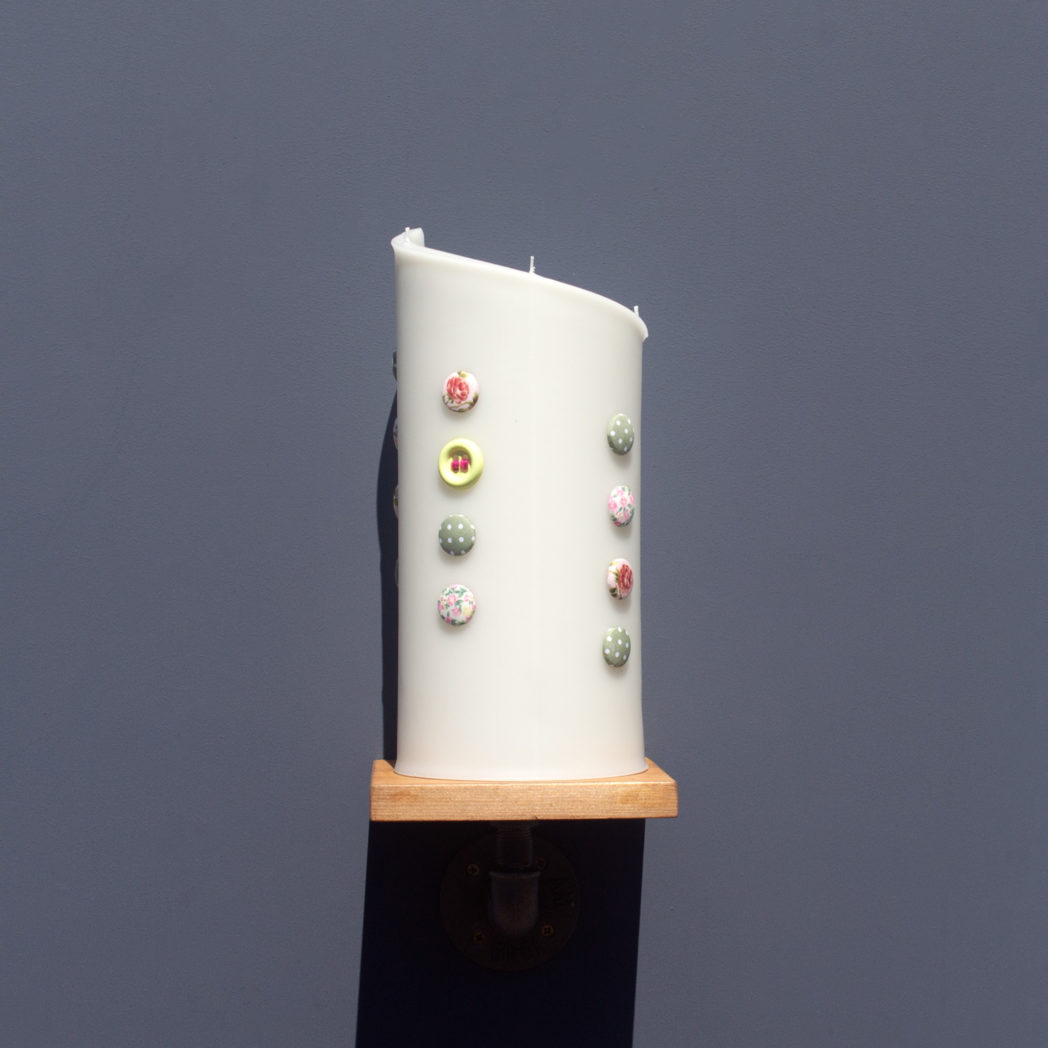 front view of ivory curve candle decorated with fabric buttons on wooden industrial pipe shelf