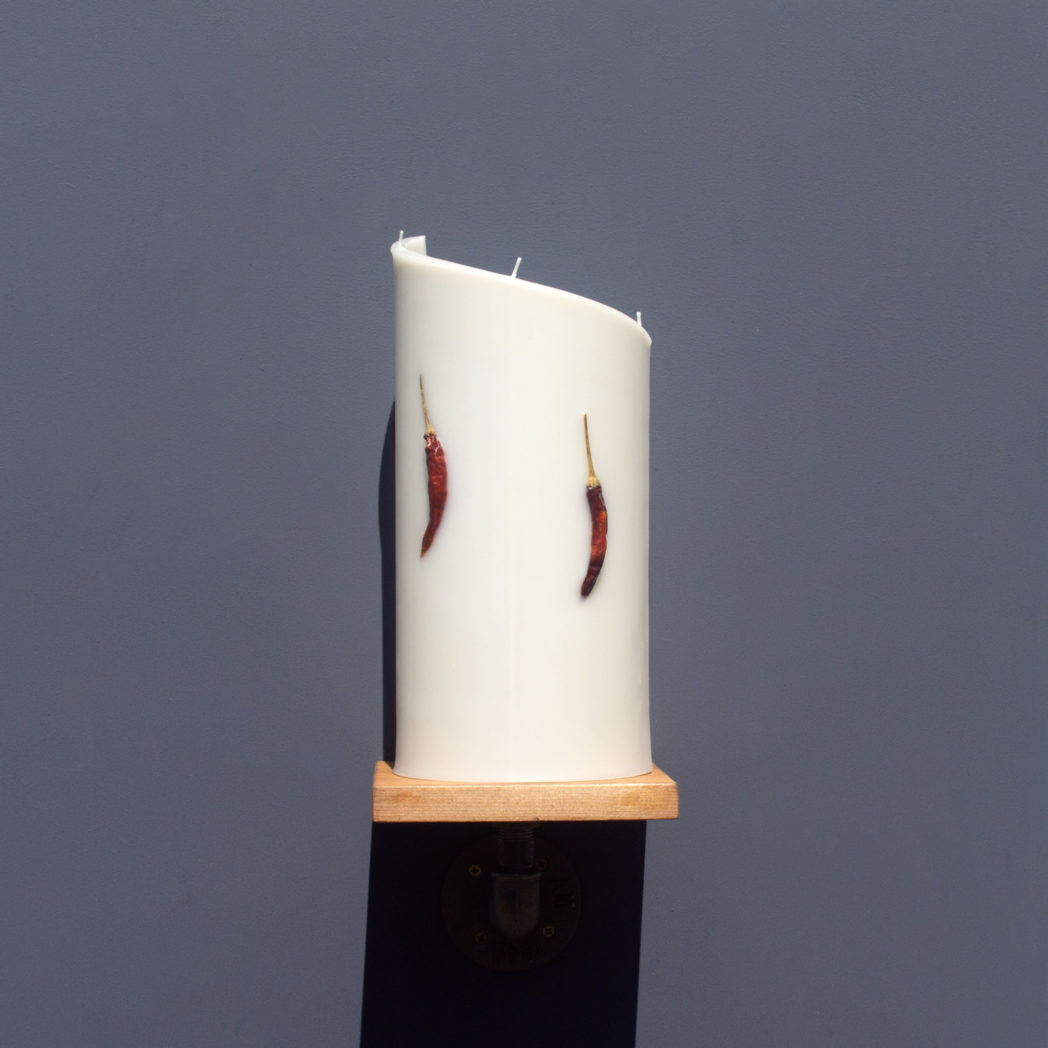 front view of ivory curve candle decorated with dried red chilli chillies on wooden industrial pipe shelf