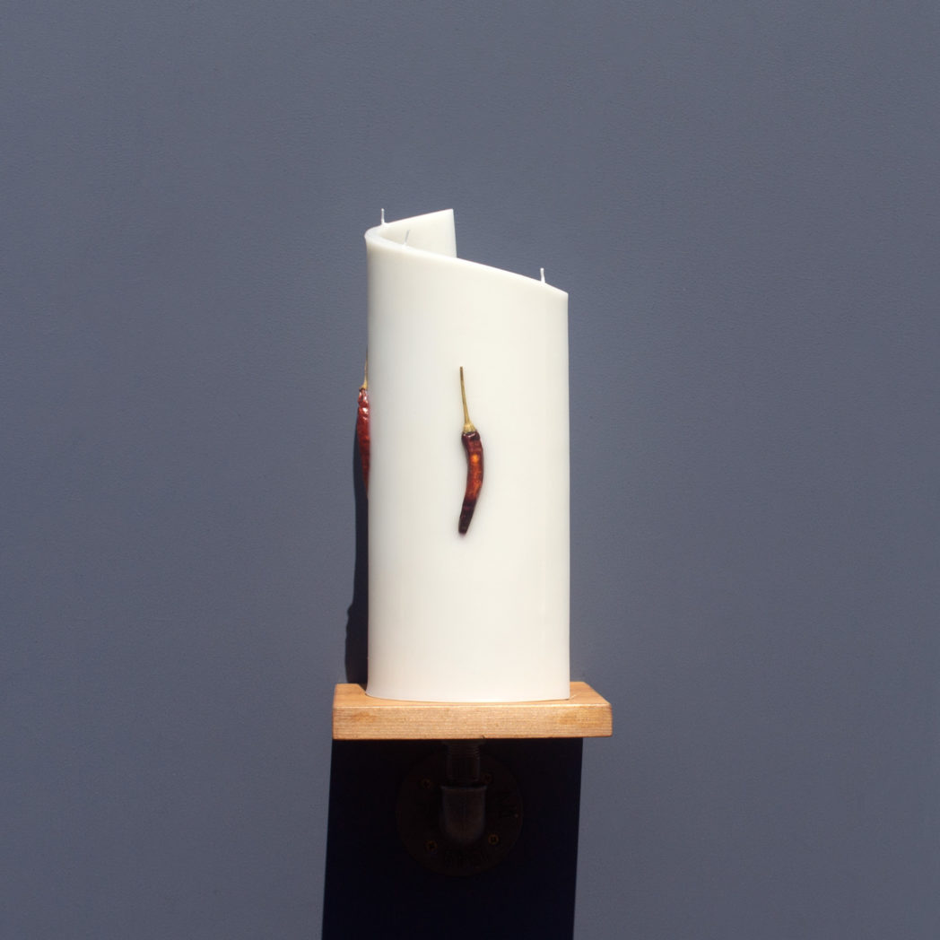 side view of ivory curve candle decorated with dried red chilli chillies on wooden industrial pipe shelf