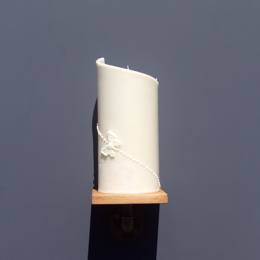 front view of ivory curve candle decorated with wax lace and butterfly on wooden industrial pipe shelf