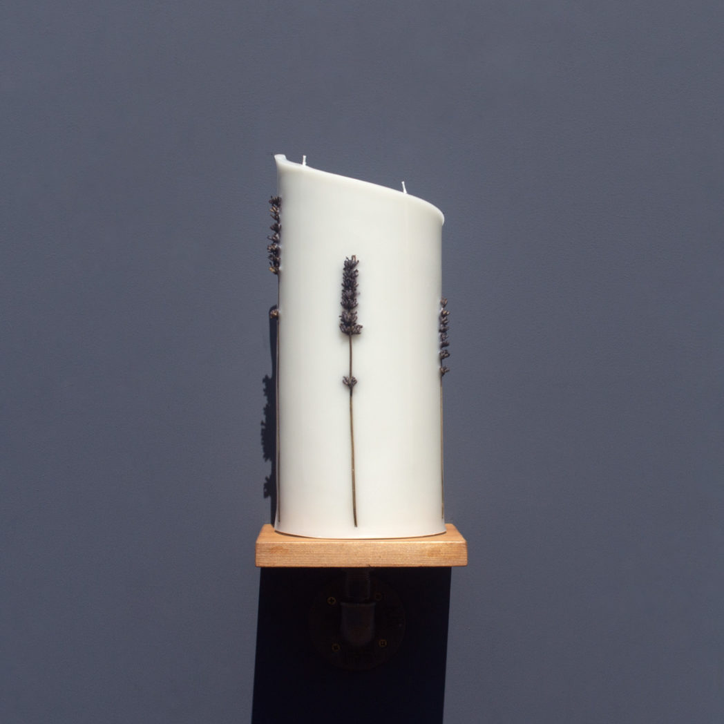 front view of ivory curve candle decorated with stems of dried lavender on wooden industrial pipe shelf