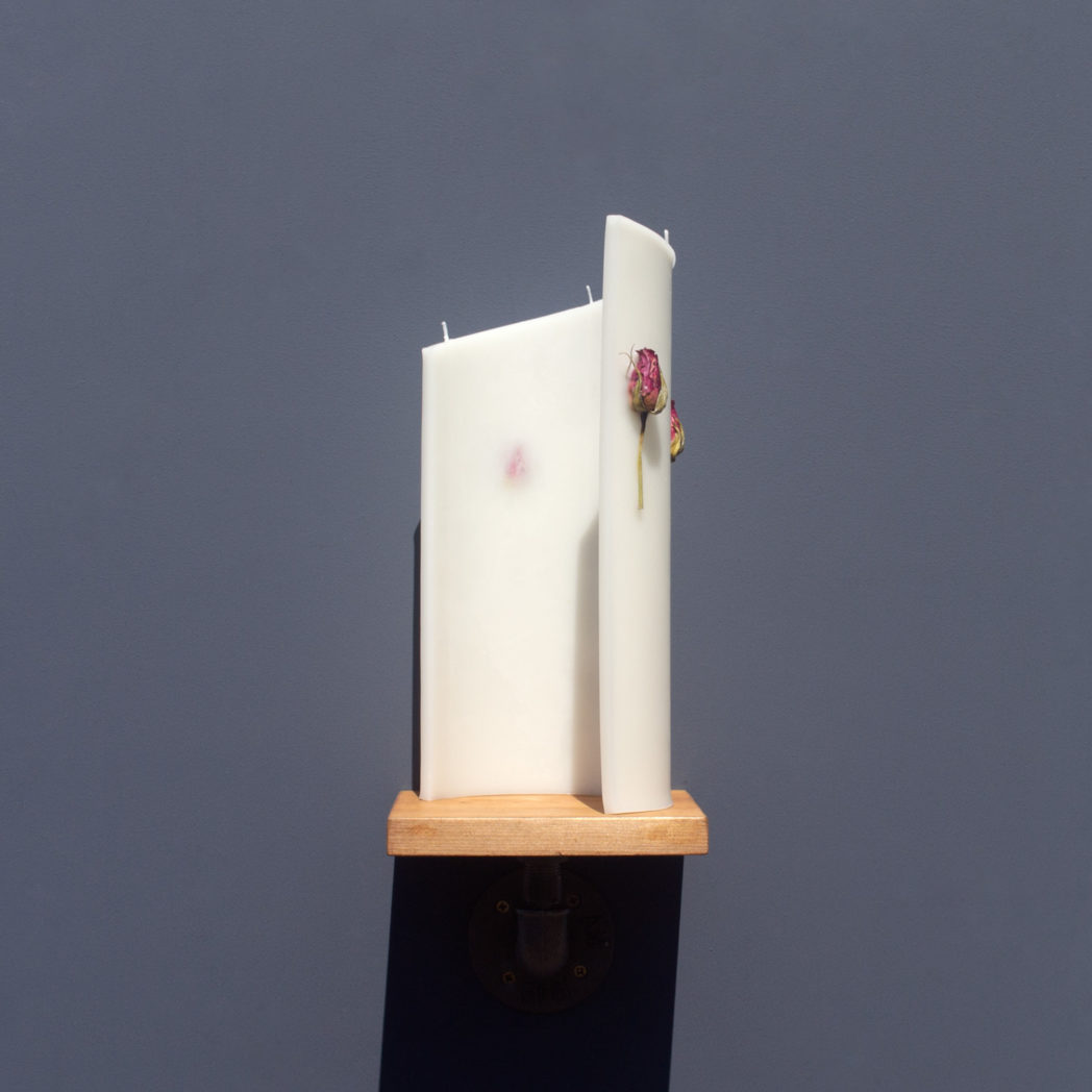 ivory curve candle decorated with dried cerise rose stems from behind on wooden industrial pipe shelf