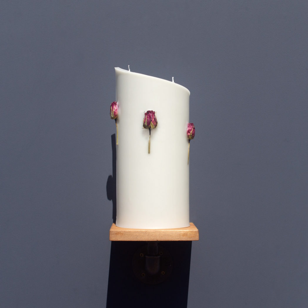 front view of ivory curve candle decorated with dried cerise rose stems on wooden industrial pipe shelf