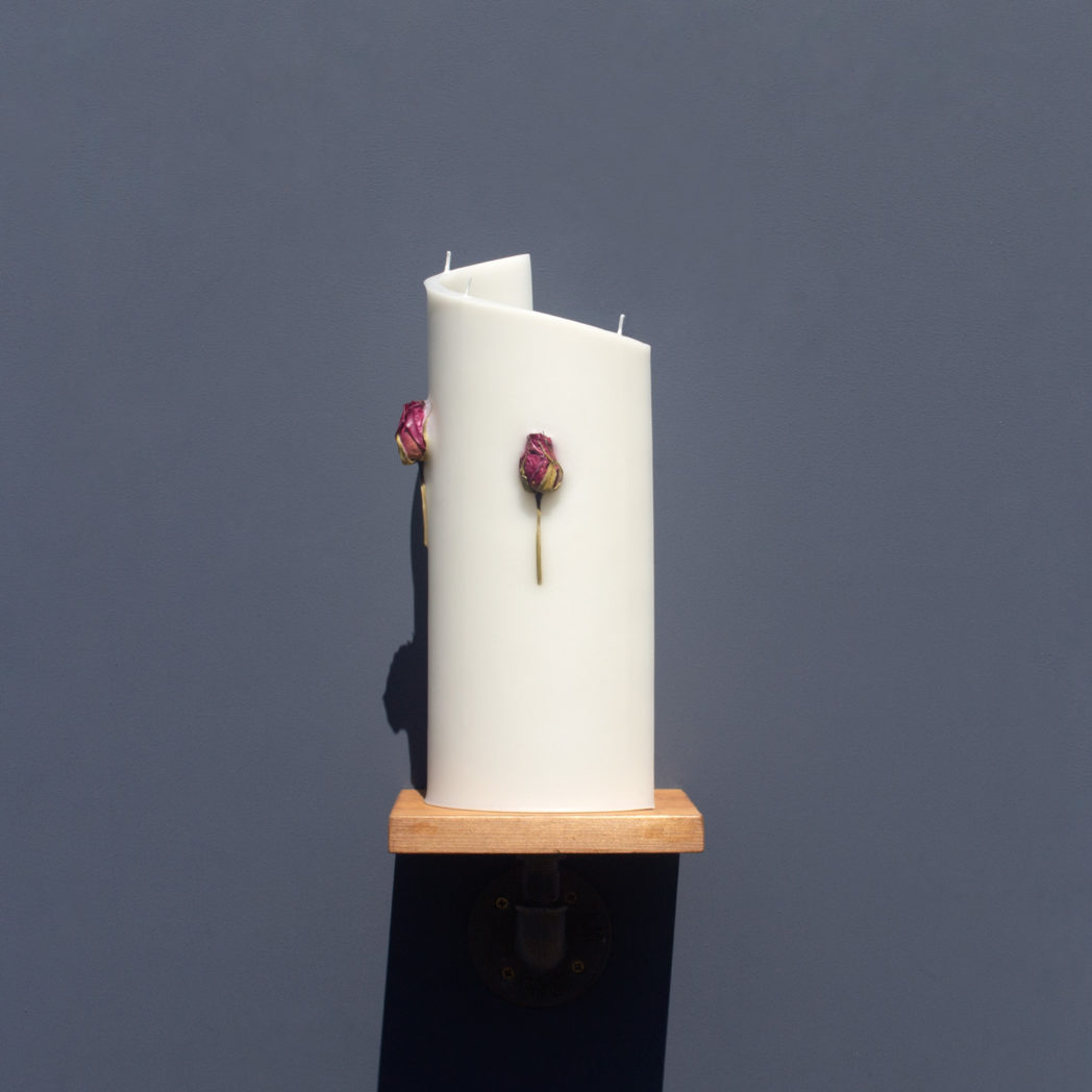 side view of ivory curve candle decorated with dried cerise rose stems on wooden industrial pipe shelf