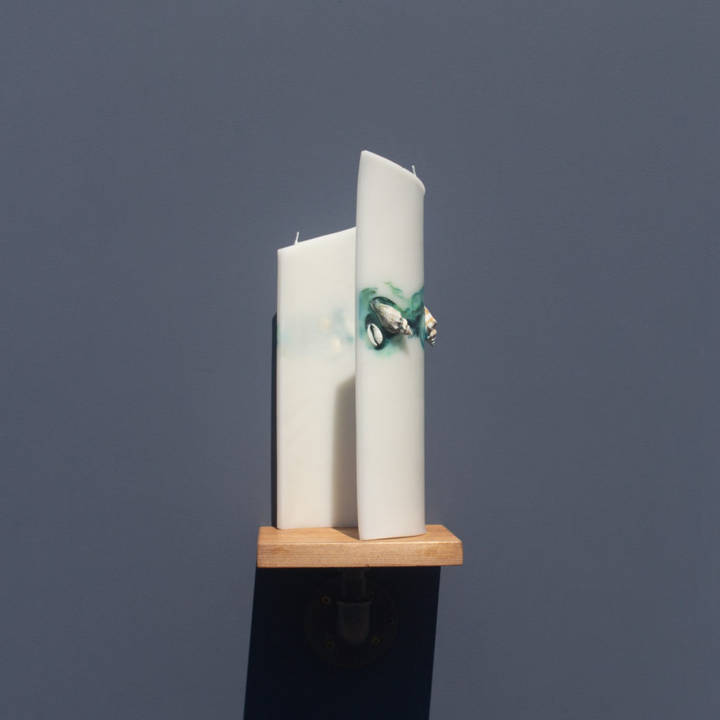 ivory curve candle decorated with shells and marbled green and blue wax from behind on wooden industrial pipe shelf