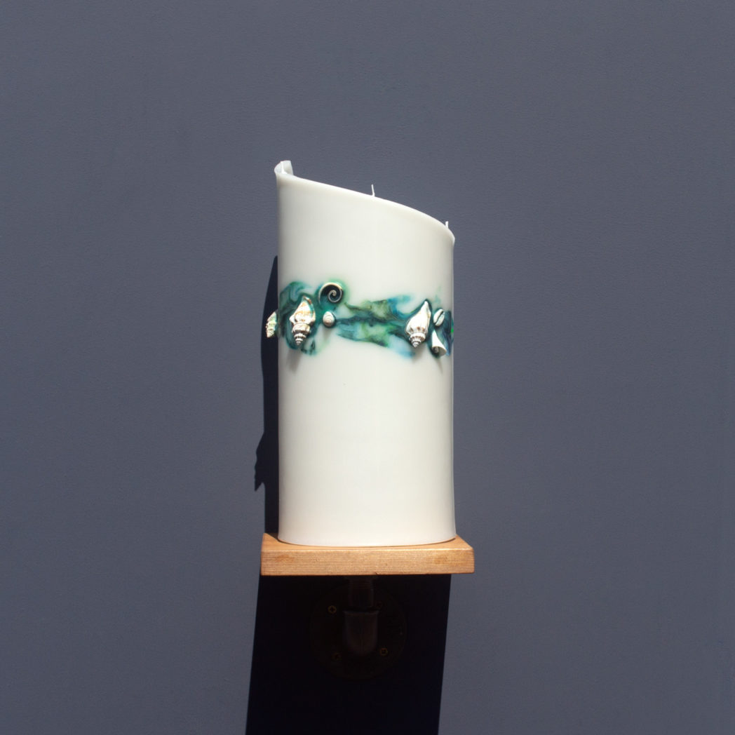 front view of ivory curve candle decorated with shells and marbled green and blue wax on wooden industrial pipe shelf
