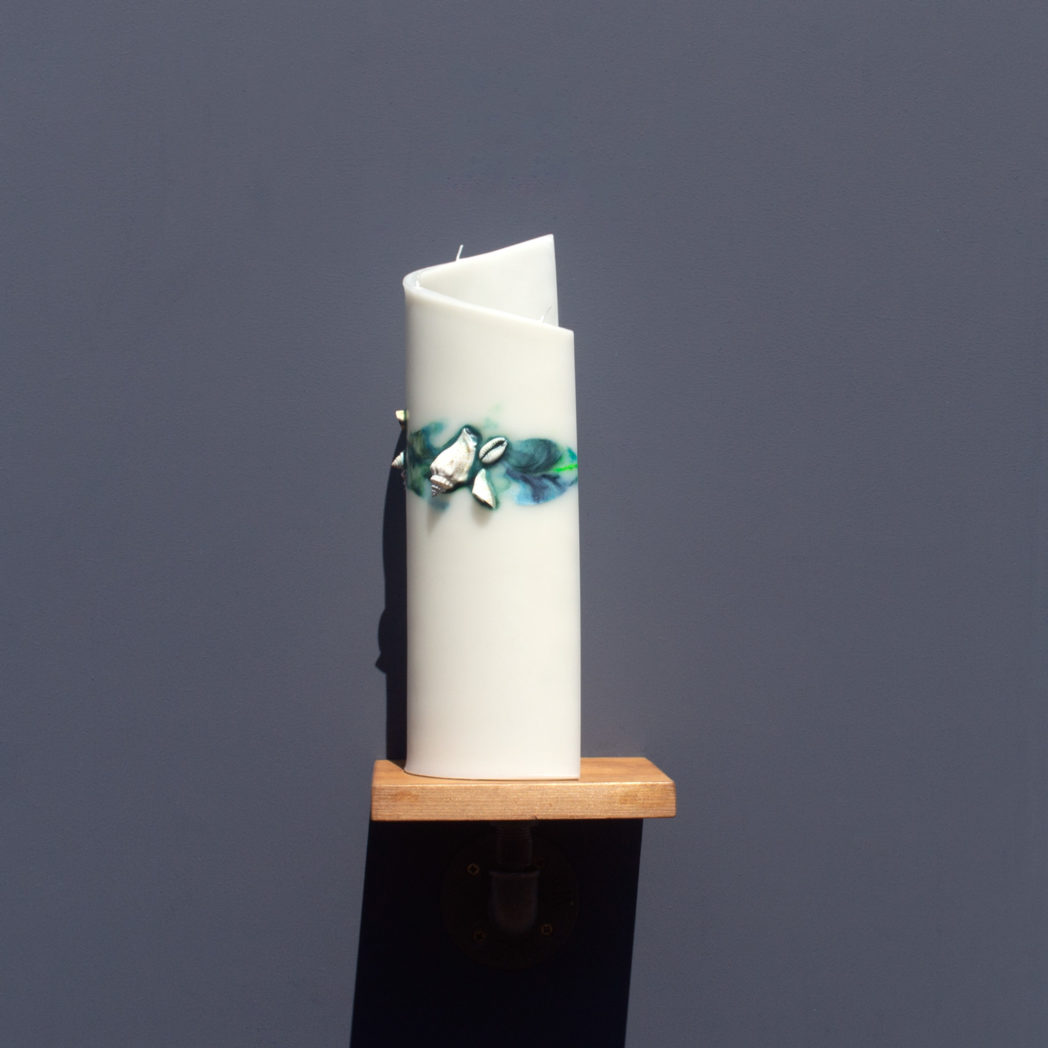side view of ivory curve candle decorated with shells and marbled green and blue wax on wooden industrial pipe shelf