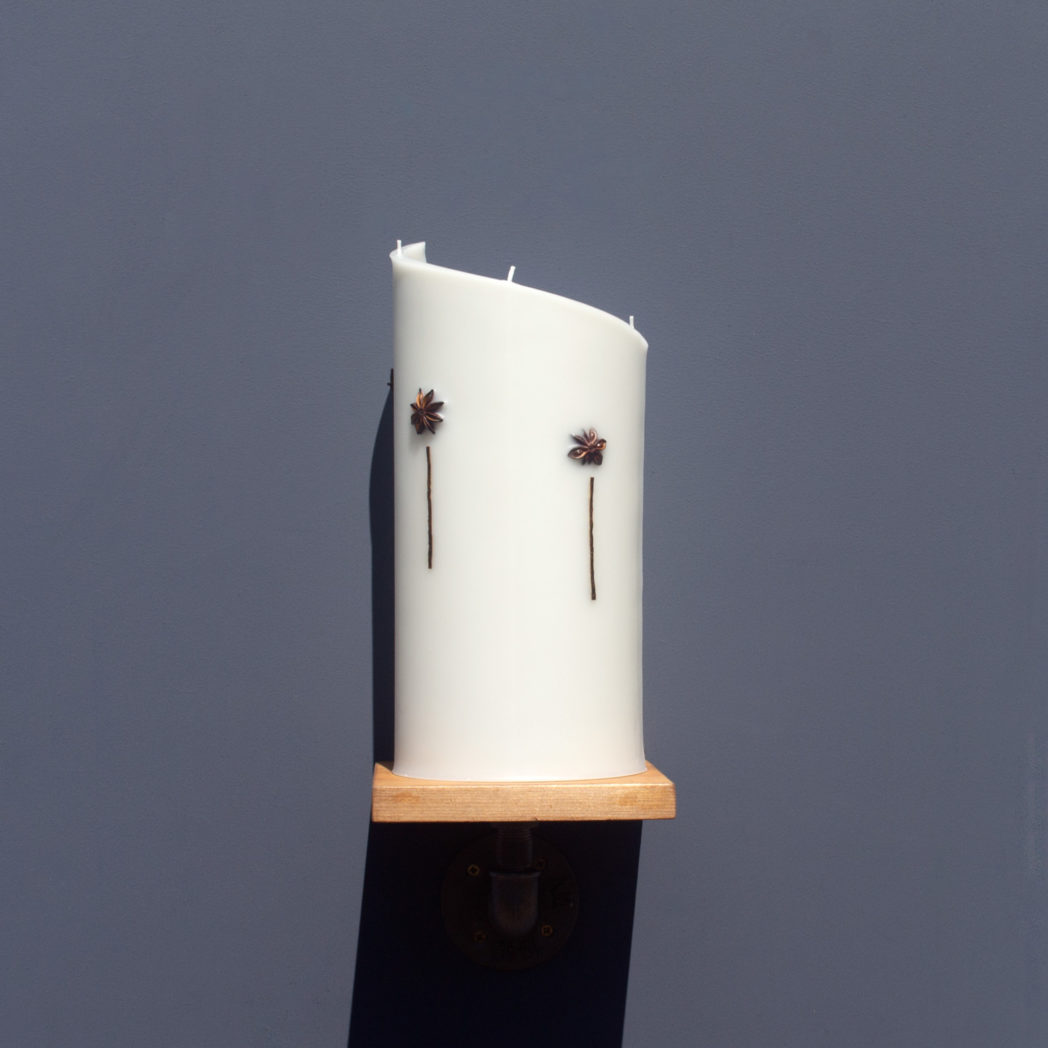 front view of ivory curve candle decorated with star anise and vanilla pod on wooden industrial pipe shelf